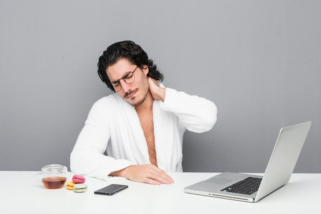 座りがちな生活のために首の痛みに苦しんでいるシャワーの後に働く若いハンサムな男。 Premium写真