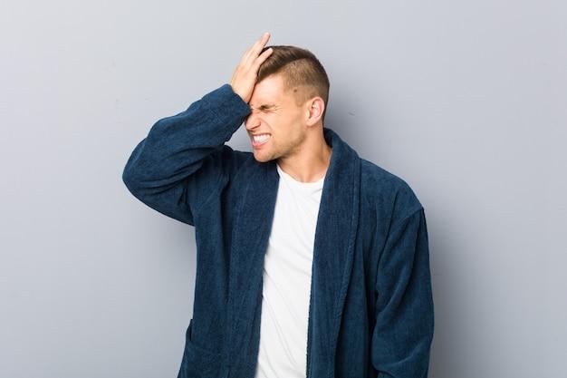 Пижама молодого кавказского человека нося забывая что-то, шлепая лоб с ладонью и закрывая глаза. Premium Фотографии