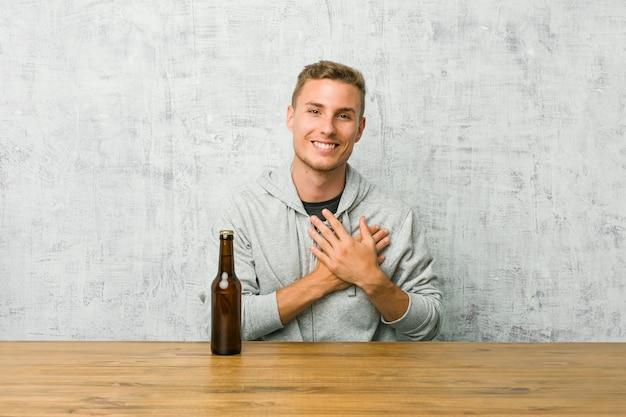 テーブルでビールを飲む若い男は、手のひらを胸に押し付ける、フレンドリーな表情を持っています。コンセプトが大好きです。 Premium写真