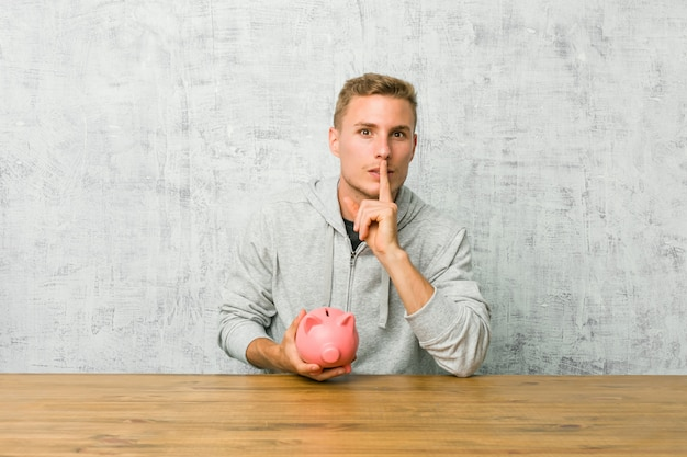 若い男が秘密を守るか沈黙を求めて貯金箱でお金を節約します。 Premium写真
