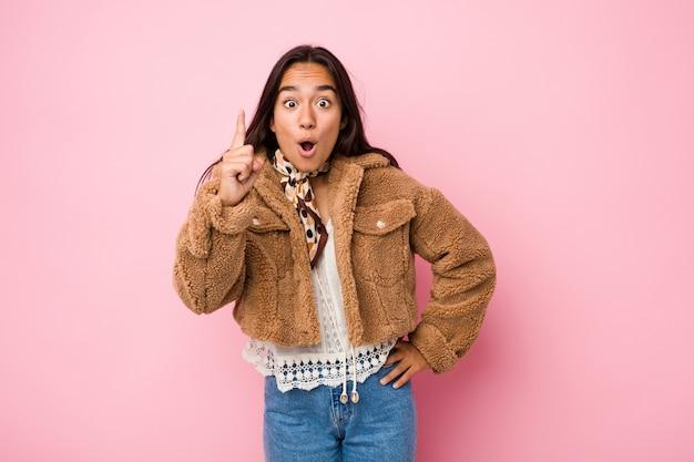 アイデア、インスピレーションのコンセプトを持つ短いムートンコートを着ている若い混血インドの女性。 Premium写真