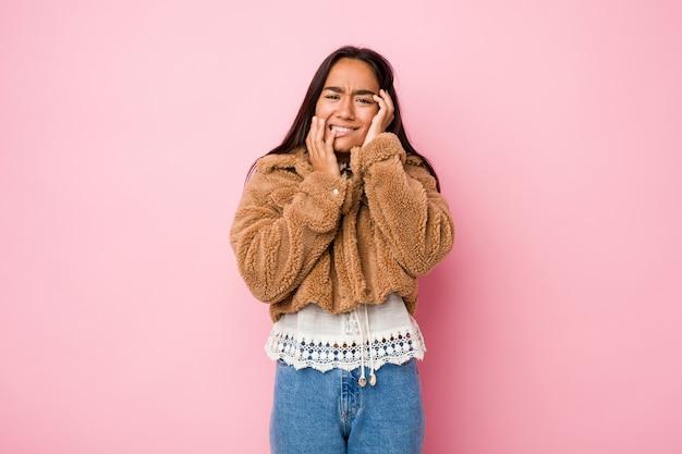 若い混血インドの女性は、短い羊皮のコートを身に着けて泣き叫び、孤独に泣いています。 Premium写真
