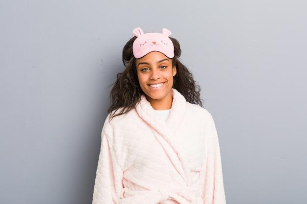 Молодая афро-американская женщина нося пижаму и маску сна счастливую, усмехающся и жизнерадостная. Premium Фотографии