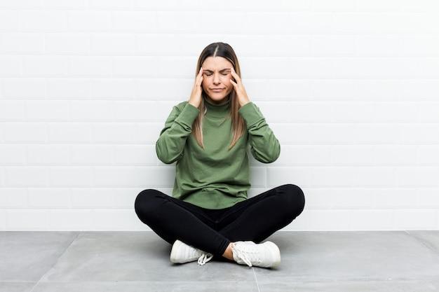 Молодая кавказская женщина сидя на висках пола касающих и имея головную боль. Premium Фотографии
