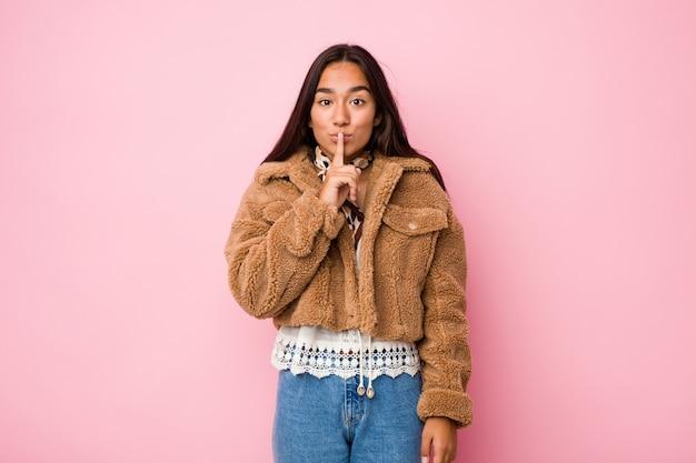 若い混血のインド人女性が秘密を守るか沈黙を求める短いシープスキンのコートを着ています。 Premium写真