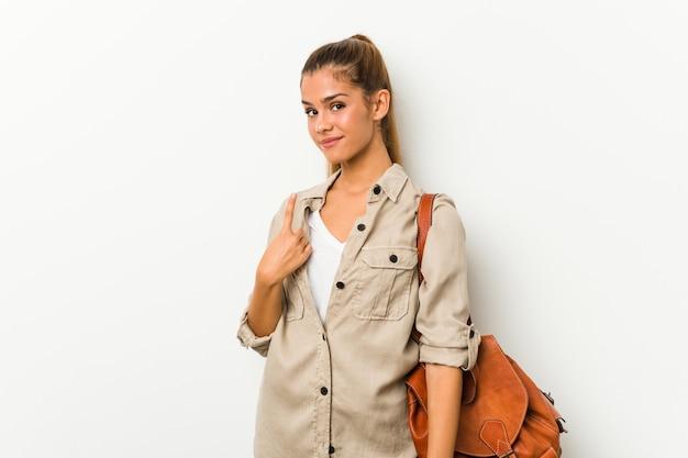 Молодая кавказская женщина готова для путешествия, указывая пальцем на вас Premium Фотографии