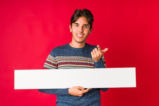 Молодой человек держит плакат, указывая пальцем на вас, как будто приглашая подойти ближе. Premium Фотографии
