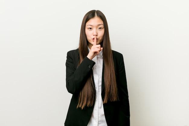 若いかなり中国のビジネス女性が秘密を守るか沈黙を求めています。 Premium写真