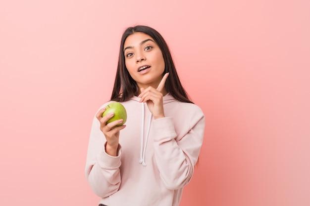 リンゴを保持している若いインド人女性 Premium写真