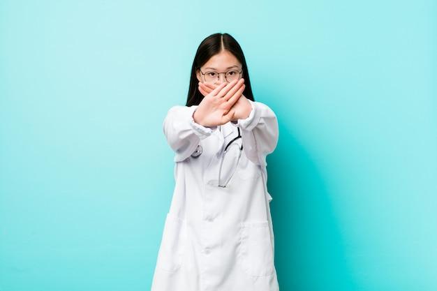 Молодая китайская женщина доктора делая жест отказа Premium Фотографии