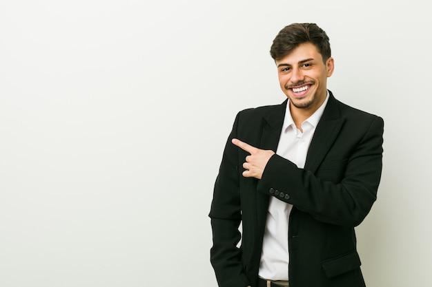 若いビジネスヒスパニック男笑顔とさておき、空白スペースで何かを示します。 Premium写真
