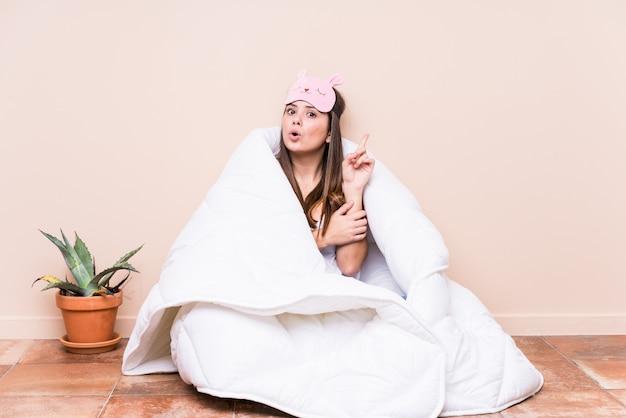 いくつかの素晴らしいアイデア、創造性の概念を持つキルトで休む若い白人女性。 Premium写真