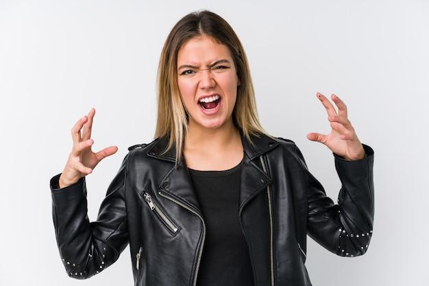 Молодая кавказская женщина нося черную кожаную куртку кричащую с яростью. Premium Фотографии