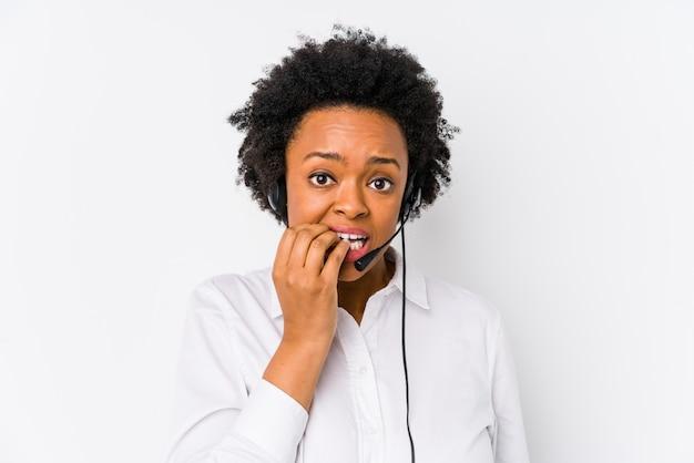 Молодая афро-американская женщина телемаркетера изолировала кусая ногти, нервная и очень тревожная. Premium Фотографии