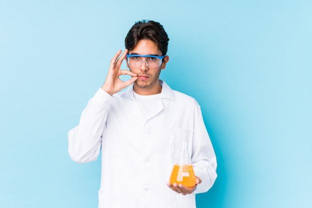 Молодой научный кавказский человек изолировал с пальцами на губах держа в секрете. Premium Фотографии