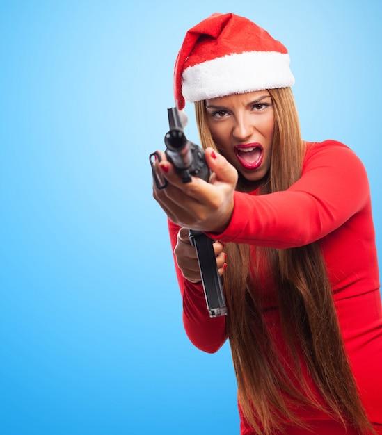 サンタの帽子とピストルを持つ若い女性 無料写真