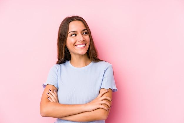 組んだ腕に自信を持って笑顔のスキー服を着た若い白人女性が分離されました。 Premium写真