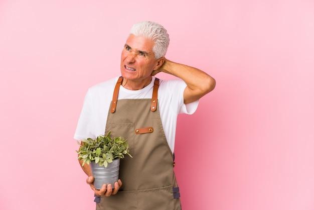 中年の庭師の男は、頭の後ろに触れて考え、選択を分離しました。 Premium写真