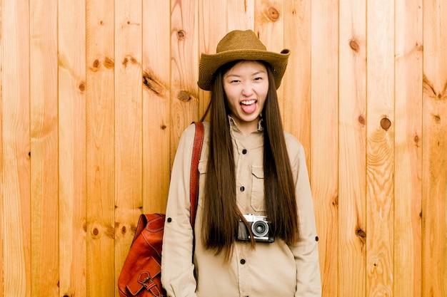 舌を突き出して面白いとフレンドリーな若い中国人旅行者の女性。 Premium写真