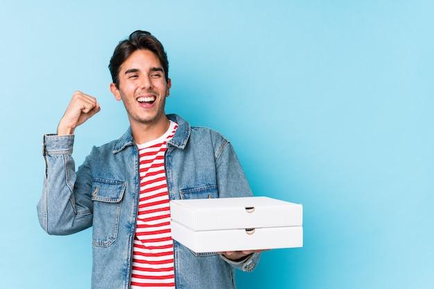 ピザを保持している若い白人男は、勝利、勝者の概念の後拳を上げる分離しました。 Premium写真