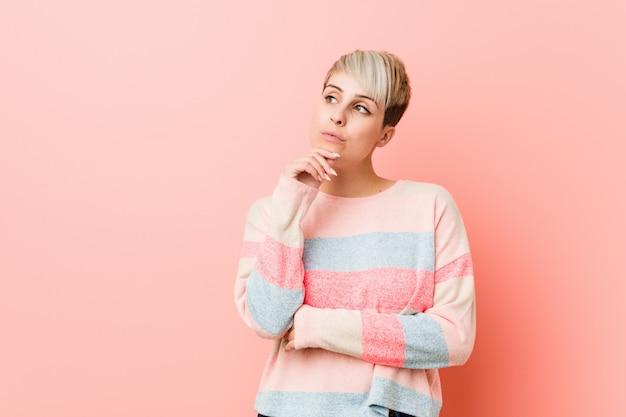 疑わしいと懐疑的な表情で横に見て若い自然な曲線の女性。 Premium写真