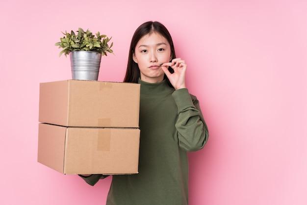 Молодая китайская женщина держа коробки изолированный с пальцами на губах держа секрет. Premium Фотографии