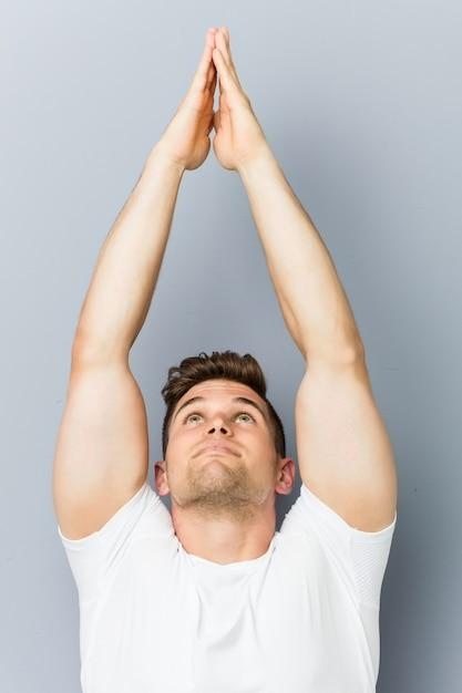 屋内ヨガの練習の若い白人男 Premium写真