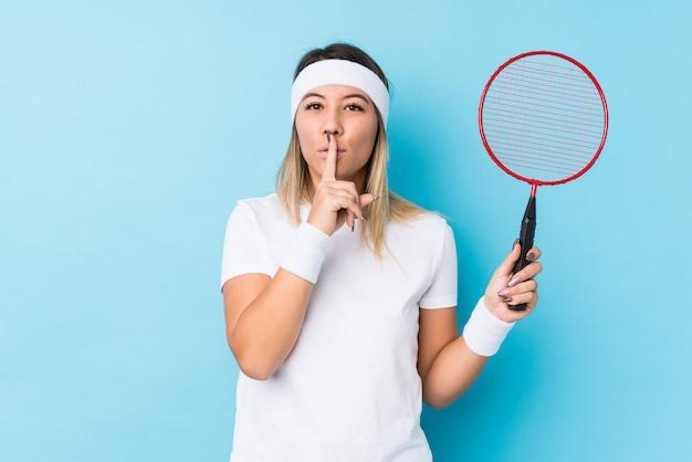 バドミントンをしている若い白人女性が秘密を守ったり、沈黙を求めて分離しました。 Premium写真