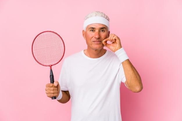 Человек постаретый серединой играя бадминтон изолированный с пальцами на губах держа секрет. Premium Фотографии