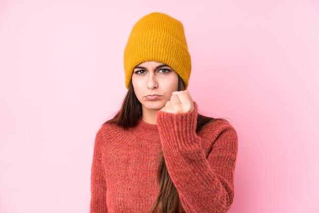 Молодая кавказская женщина нося крышку шерсти показывая кулак к с агрессивным выражением лица. Premium Фотографии
