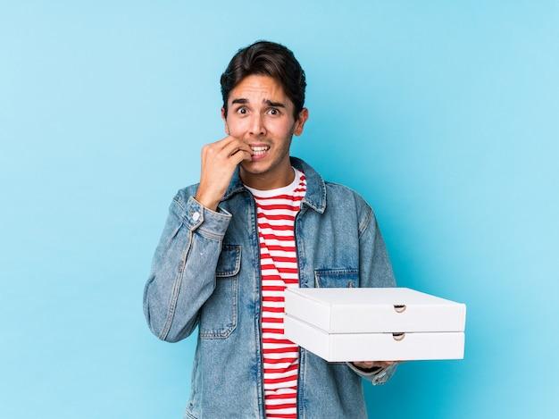 ピザを保持している若い白人男性は、神経質で非常に不安な噛み爪を分離しました。 Premium写真