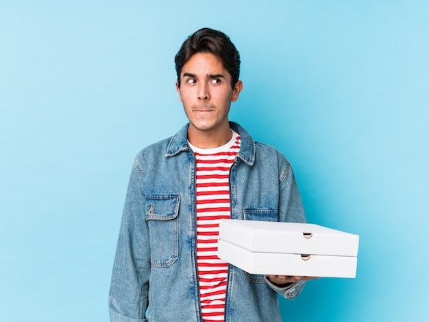 分離されたピザを保持している若い白人男は混乱し、疑わしく不安を感じています。 Premium写真