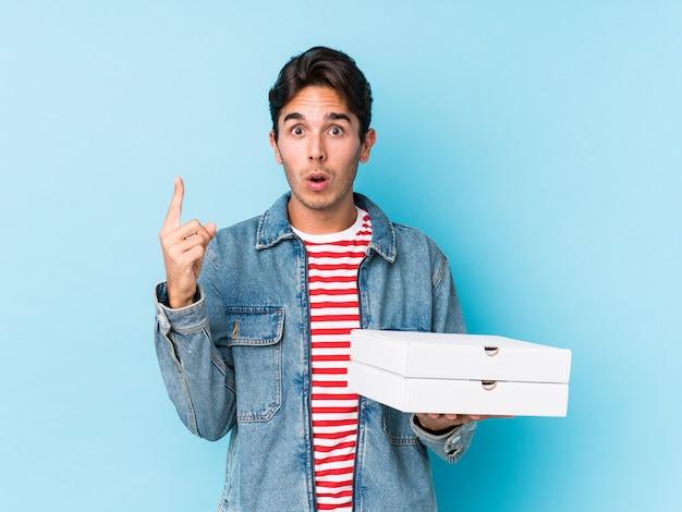 いくつかの素晴らしいアイデア、創造性の概念を持つピザを保持している若い白人男。 Premium写真