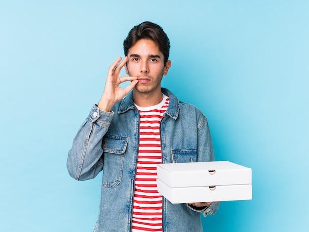 秘密を保つ唇に指で分離されたピザを保持している若い白人男。 Premium写真