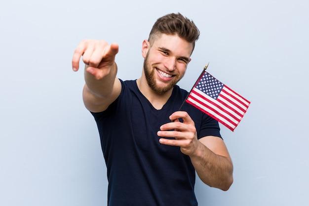 アメリカ合衆国を保持している若い白人男は正面を向いて陽気な笑顔をフラグします。 Premium写真