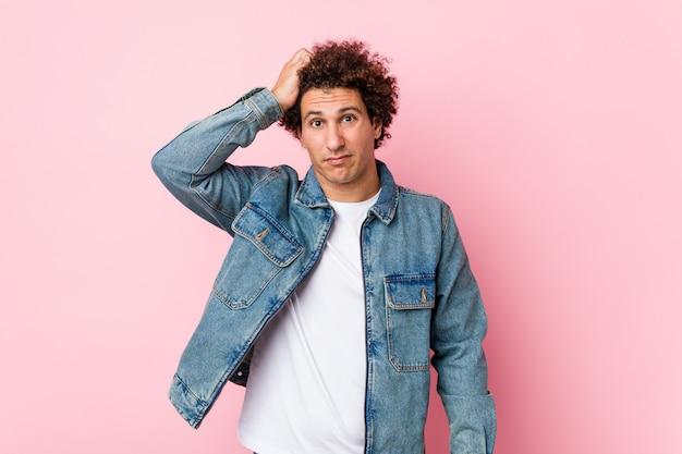 ショックを受けているピンクの壁にデニムジャケットを着ている巻き毛の成熟した男、彼女は重要な会議を覚えています。 Premium写真