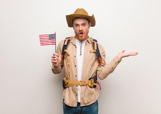 手のひらに何かを保持している若い赤毛エクスプローラー男。アメリカ合衆国のフラグを保持しています。 Premium写真