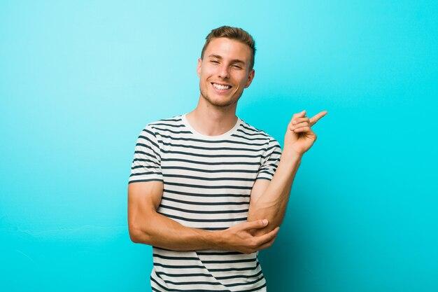 人差し指で元気に指している笑みを浮かべて青い壁に若い白人男。 Premium写真