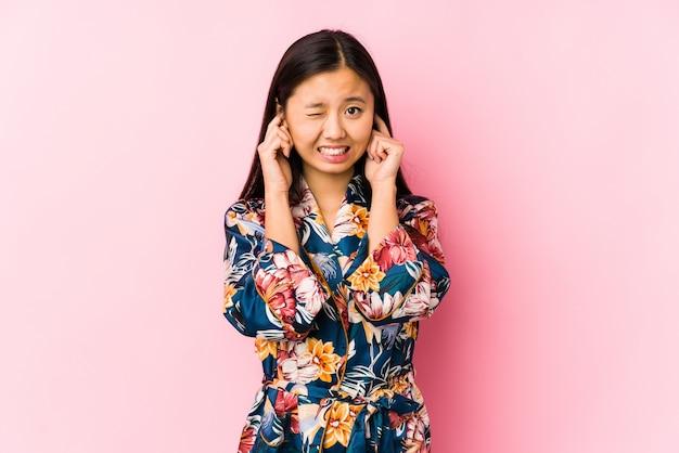 手で耳を覆って分離した着物パジャマを着ている若い中国人女性。 Premium写真