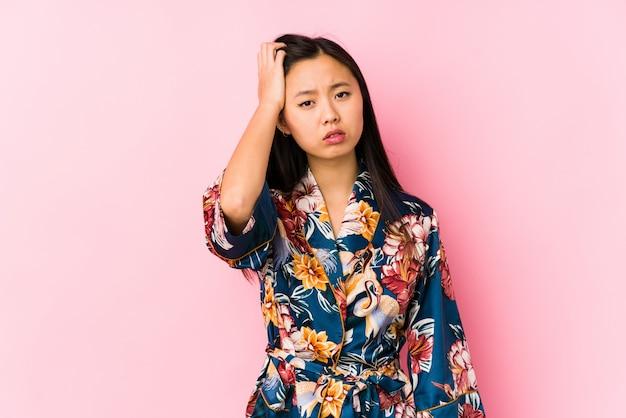 着物のパジャマを着た若い中国人女性が、疲れて非常に眠く、手を握りしめている。 Premium写真