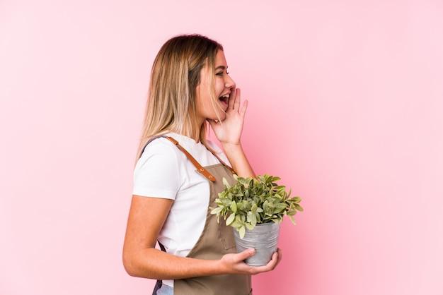 叫び、開いた口の近くの手のひらを保持しているピンクの壁の若い白人の庭師の女性。 Premium写真