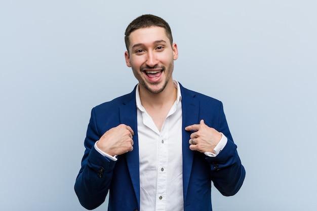 Молодой человек кавказской бизнес удивлен, указывая на себя, широко улыбаясь. Premium Фотографии