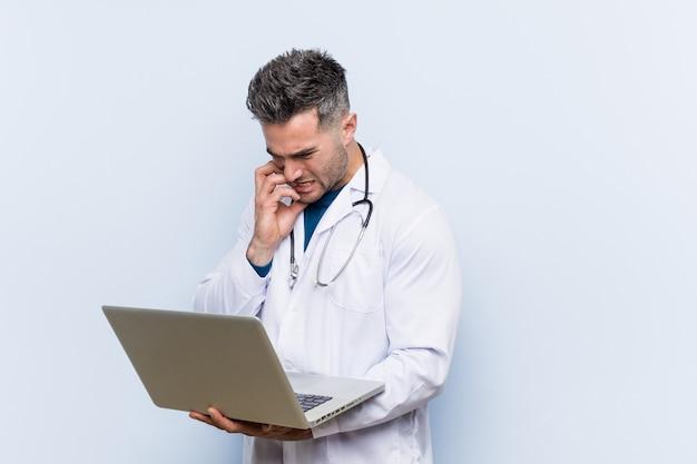 白人の医者の男は、爪をかむ、緊張し、非常に心配しているラップトップを保持しています。 Premium写真