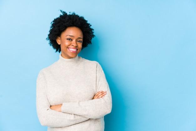 交差した腕に自信を持って笑みを浮かべて分離された青い壁の中年のアフリカ系アメリカ人女性。 Premium写真
