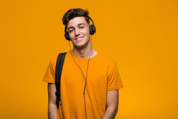 Молодой крутой студент человек слушает музыку в наушниках, улыбаясь и поднимая палец вверх Premium Фотографии