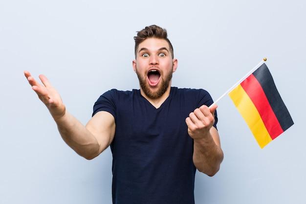 勝利または成功を祝っているドイツの旗を保持している若い白人男 Premium写真