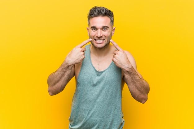 黄色の壁に対して若いフィットネス男笑顔、口で指を指しています。 Premium写真