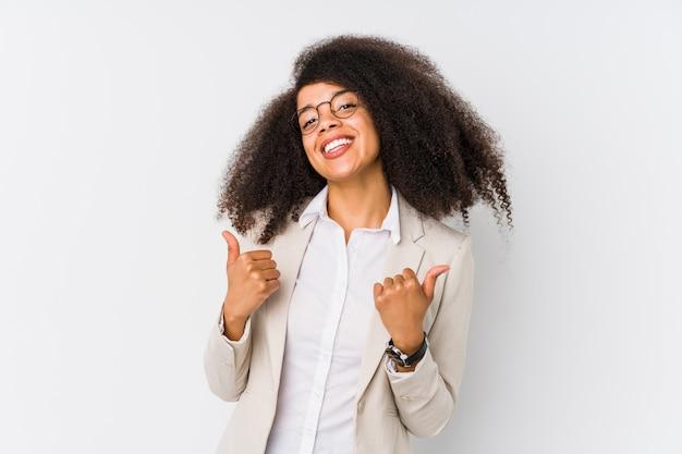Молодая афро-американская бизнес-леди поднимая оба больших пальца руки вверх, усмехаться и уверенно. Premium Фотографии