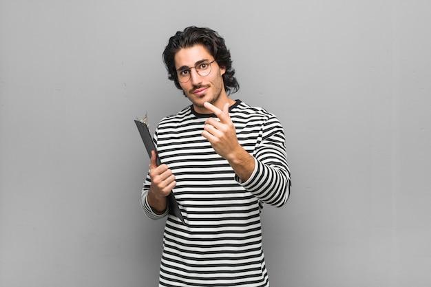 あなたを指で指している在庫を保持している若い従業員の男は、まるで招待が近づくように。 Premium写真