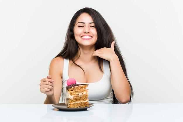 キャロットケーキを食べる若いヒスパニック系女性 Premium写真
